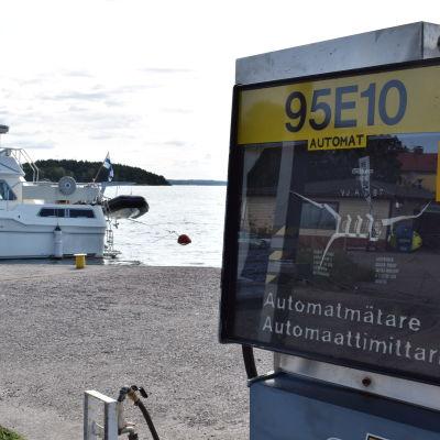 En bränslepump i en gästhamn, en större motorbåt i bakgrunden, soligt väder.