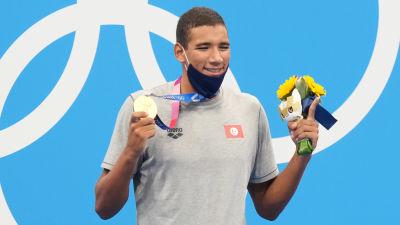 Ahmed Hafnaoui poserar med guldmedalj och blommor.