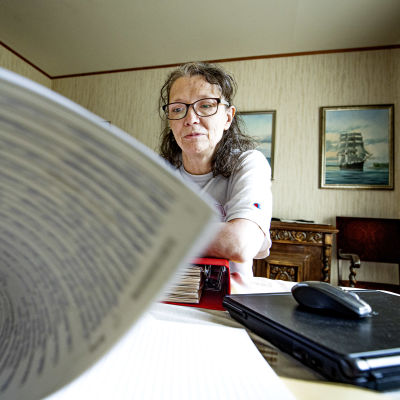 En kvinnna bläddrar i papper. I bakgrunden en tavla med en segelbåt.
