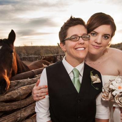 Kvinnligt brudpar poserar kind mot kind, i bakgrunden står en häst