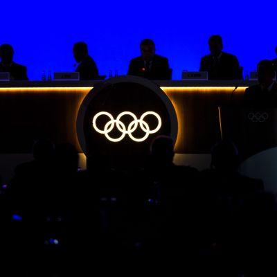 Olympiska ringarna lyser i ett bord. Vid bordet ser man en mörk siluett av internationella olympiska kommittén.