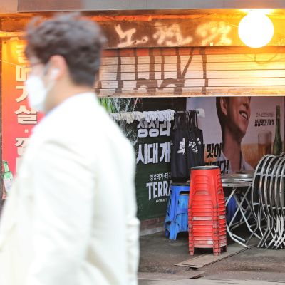 Suojamaskiin pukeutunut mies kulkee kadulla suljetun näkoisen tilan ohi.