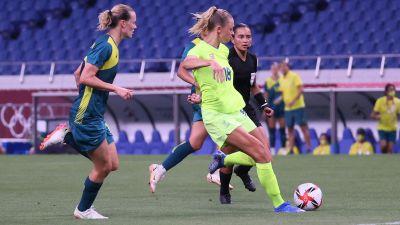 Fridolina Rolfö skjuter i väg bollen, omgiven av två australiska spelare.