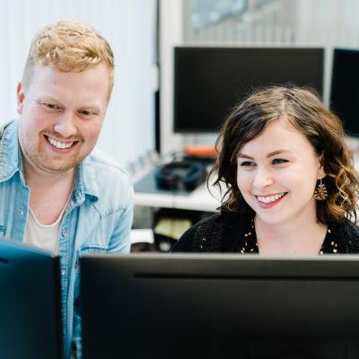 Mies ja nainen katsovat tietokoneen kahta ruutua hymyillen. Kuva on otettu tietokoneen näyttöjen takaa.