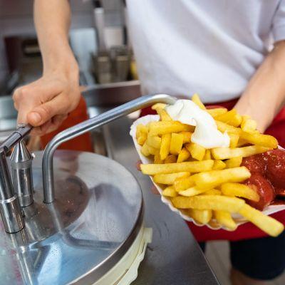En anställd vid en snabbmatsrestaurang lägger majonnäs på pommes frites.