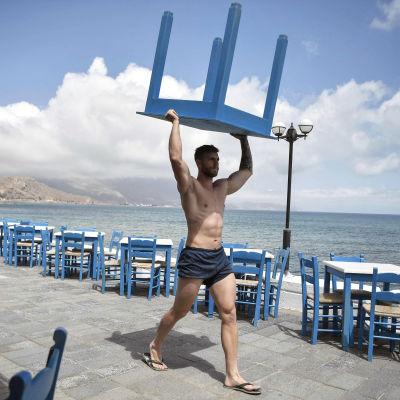 Työntekijä kantaa pöytää Kreikassa.
