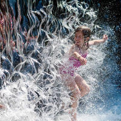 En flicka i en fontän under värmeböljan i nordamerika.