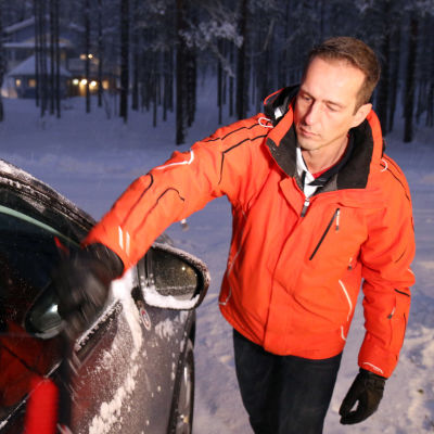 Karri Leskinen puhdistaa autoaan lumesta Kittilän Levillä.