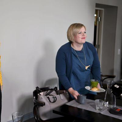 Katri Kulmuni och Annika Saarikko på dagens presskonferens. Kulmuni tar av sig jackan medan Saarikko ler mot kameran.
