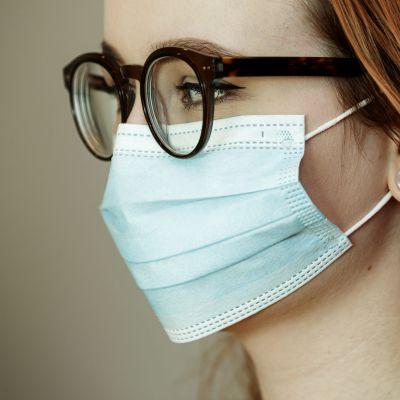 En kvinna i ansiktsskydd och glasögon.