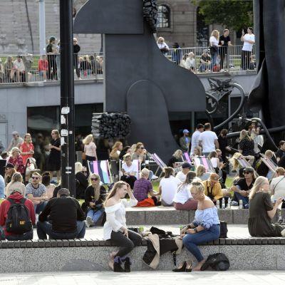Ihmiset nauttivat kauniista kesäpäivästä Musiikkitalon edustalla Helsingissä