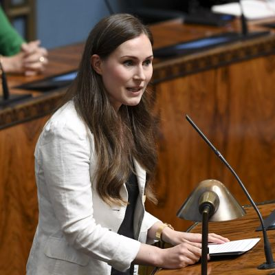 Sanna Marin i vit kavaj står i riksdagens talarstol.