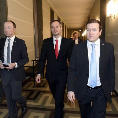 Jussi Halla-aho, Kai Mykkänen och VIlle Tavio går bredvid varandra i en korridor.