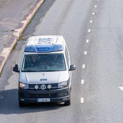 Poliisin partioauto liikenteessä kadulla.