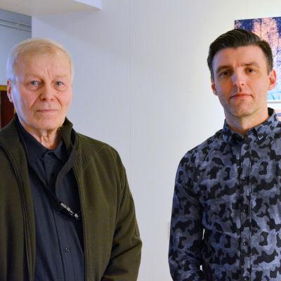 Göran Strömfors och Janne Hyöty står framför en vägg med tavlor.
