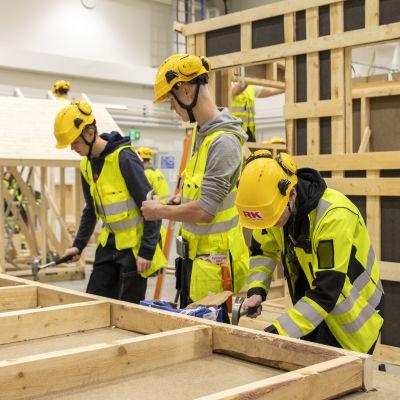 Rakennuspuolen opiskelijoita rakentamassa saunaelementtejä
