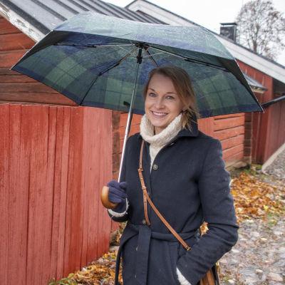 Tanja Holmberg står framför en rad med gamla hus i Borgås Gamla stan.