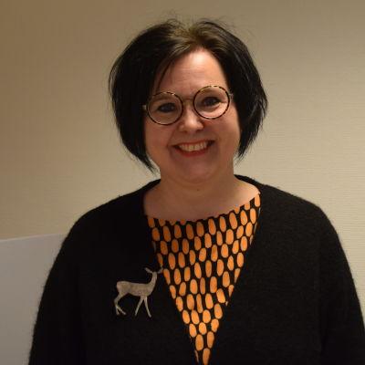 En kvinna med mörkt hår och runda glasögon.  Ser glad ut.