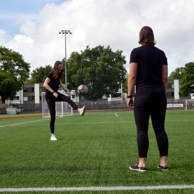 Två unga kvinnor står och sparkar fotboll på en konstgräsplan.