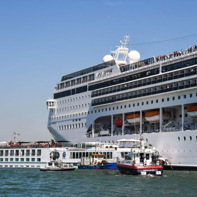 Det stora kryssningsfartyget bredvid turistbåten och sjöräddningens båtar.