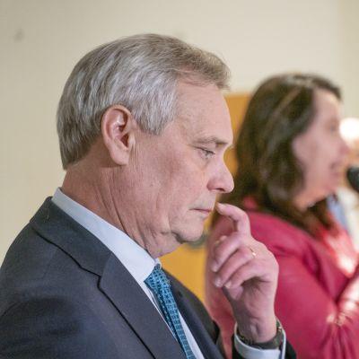 Statsminister Antti Rinne i profil. Han ser ner i golvet och har handen lyft och sitt finger under näsan.