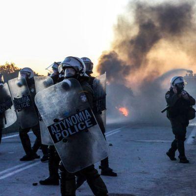 Grekisk kravallpolis intill en av de vägspärrar som demonstranter byggt upp i närheten av staden Madamados, på Lesbos, på tisdag morgon.