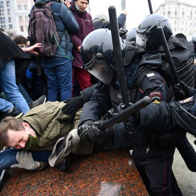 Polis i kravalluniform slår demonstranter med batonger.