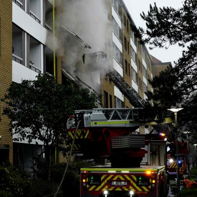 Rök stiger från ett flervåningshus, brandbilar bredvid.