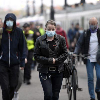 Personer bär munskydd på tågstationen i Helsingfors.
