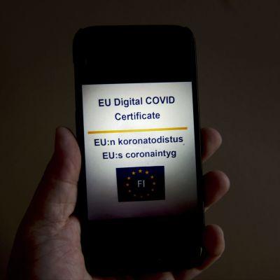 Mobiltelefon med EU:s coronaintyg på skärmen. Intyget kan laddas ner i mobilen från webbplatsen kanta.fi.