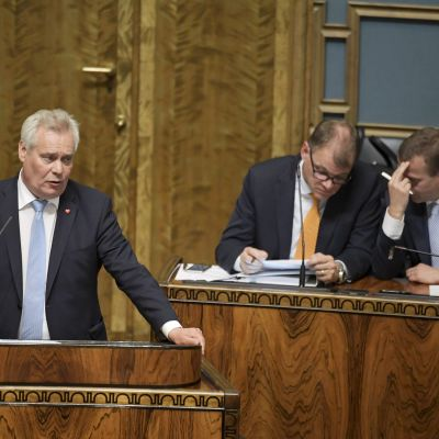 Antti Rinne håller sitt anförande medan Juha Sipilä och Petteri Orpo viskar.