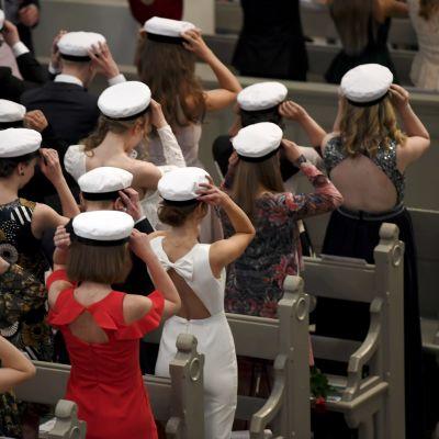 Studenter som står i bänkrader sätter på sina vita studentmössor.