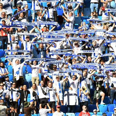 Finländska fotbollsfans med flaggor och fotbollsskjortor i S:t Petersburg.