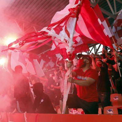 Soihdut palavat HIFK:n fanikatsomossa Töölön jalkapallostadionilla Helsingissä kauden ensimmäisessä Stadin derbyssä eli jalkapallon Veikkausliigan ottelussa HIFK - HJK 30. kesäkuuta 2021.