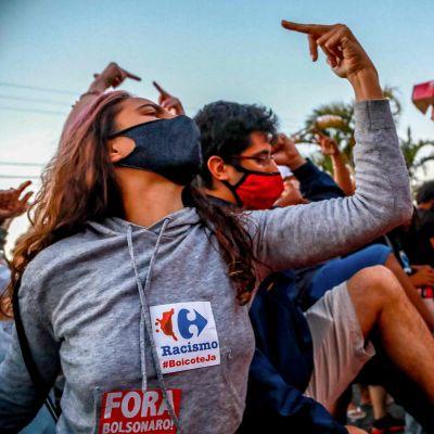 Demonstration i Porto Alegre 20.11.2020. En kvinna i munskydd håller upp sitt mittfinger.