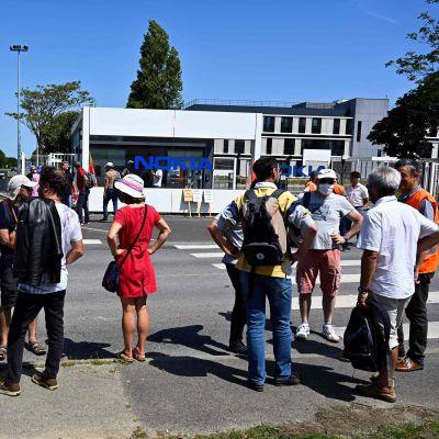 Människor står utanför ett Nokia-kontor och demonstrerar.