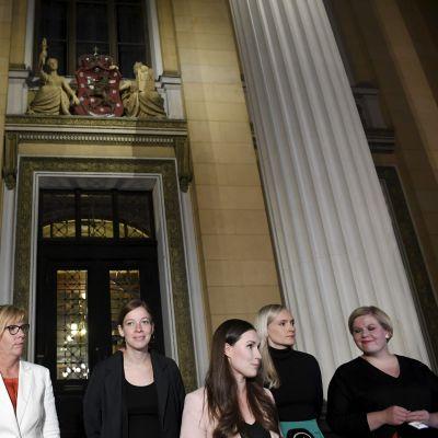Ministrarna Matti Vanhanen (till vänster), Anna-Maja Henriksson, Li Andersson, statsminister Sanna Marin, inrikesminister Maria Ohisalo och Annika Saarikko står på Ständerhusets trappa i Helsingfors.