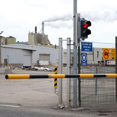 Mustakeltainen puomi ja kieltomerkkejä Stora Enson Veitsiluodon tehtaan portilla. Taustalla näkyy sellutehtaan korkea rakennus.