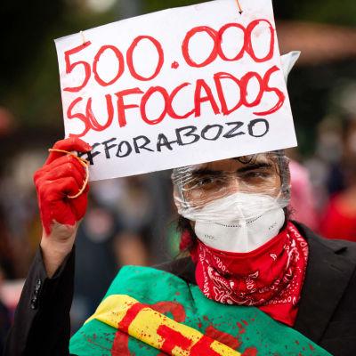 Demonstrant som håller upp en skylt med rödmålad.