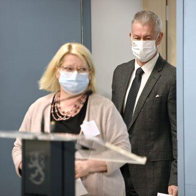 En man och en kvinna i munskydd bakom ett podium på statsrådets presskonferens.
