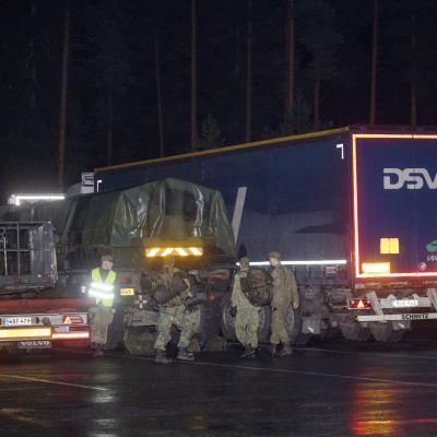 Personal från Försvarsmakten invid en långtradare på en parkeringsplats.