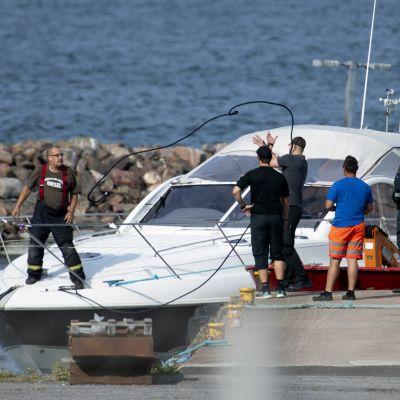 Större motorbåt vid brygga men människor kring och på båten. Olycksbåtarna på Erstan den 3 augusti 2019 transporterades till Pärnäs i Nagu.