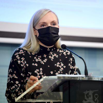 Maria Ohisalo bär en blommig, svart klänning och ett svart munskydd och står vid ett talarpodium.