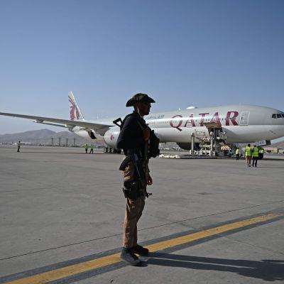En soldat står på ett flygfält med ett passagerarplan bakom sig. På planet står med stora bokstäver Qatar.