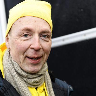 En man i gul mössa tittar leende in i kameran.