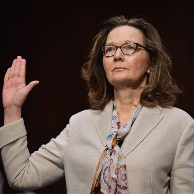 Gina Haspel i ljus dräkt och knytblus höjer höger hand, svär berätta sanningen för kongressuskottet