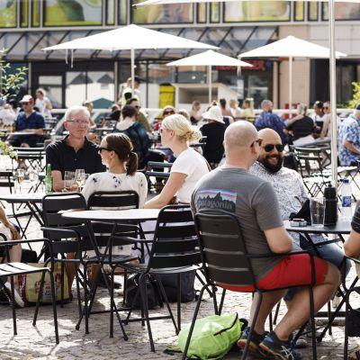 Många människor sitter på en uteservering på Kaserntorget i Helsingfors och förfriskar sig i solen.