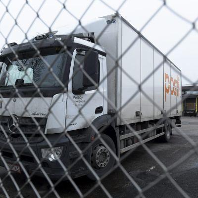 Lastbil med Postens logga står parkerad bakom ett stängsel.
