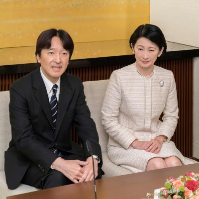 Kronprins Akishino och kronprinsessan Kiko sitter ner på två stolar, han i kostym, hon i ljus klänning.