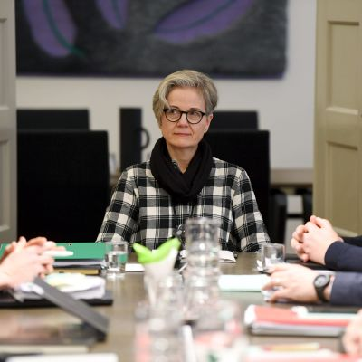 Kvinna sitter i mitten av ett bord. Kvinnan är riksförlikningsmannen Vuokko Piekkala. Bredvid henne Petri Vanhala och Jyrki Hollmén.
